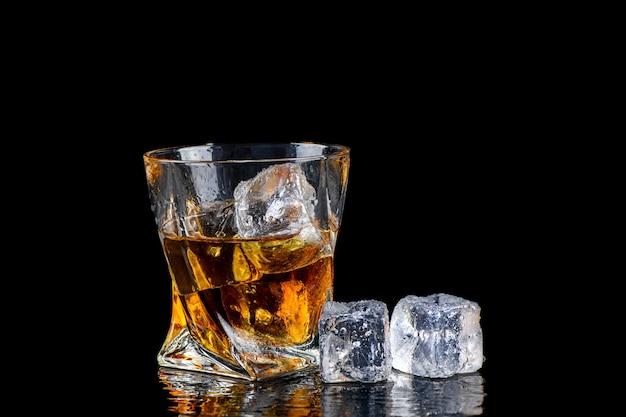 Kieliszek whisky lub innego alkoholu z kostki lodu na czarnym tle
