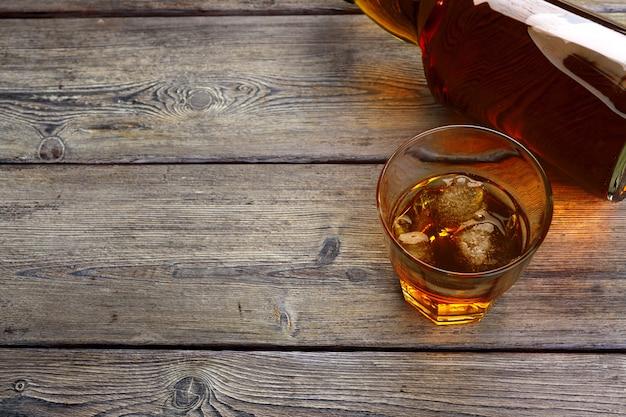 Kieliszek whisky na lodzie z butelką na pasku drewna