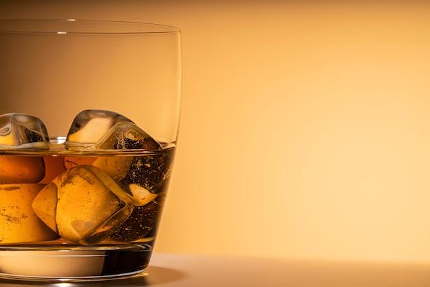 Kieliszek whisky z bliska lód skały. lub inny alkohol: bourbon, koniak lub likier. pomarańczowe tło