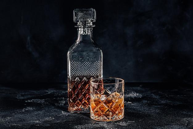 Kieliszek whisky z kwadratową karafką na czarnym tle kamienia.