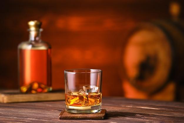 Kieliszek whisky z lodem na drewnianym stole z butelką i beczką na tle