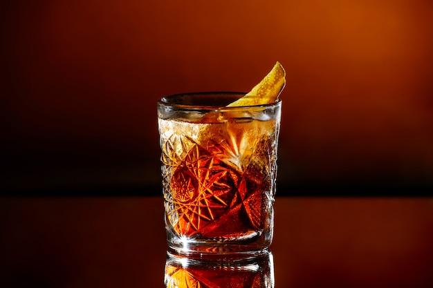 Kieliszek whisky z lodem na pomarańczowo brązowym tle.