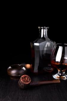 Kieliszek whisky z palącym cygarem. whisky, tytoń.