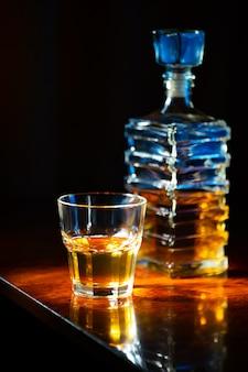 Kieliszek whisky ze starą kwadratową karafką na lakierowanym drewnianym stole