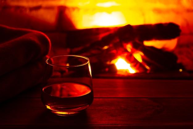 Kieliszek wina alkoholowego przed kominkiem. magiczna zrelaksowana przytulna atmosfera w pobliżu ognia