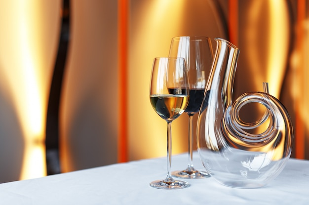 Kieliszek wina i karafka na stole z białym obrusem.