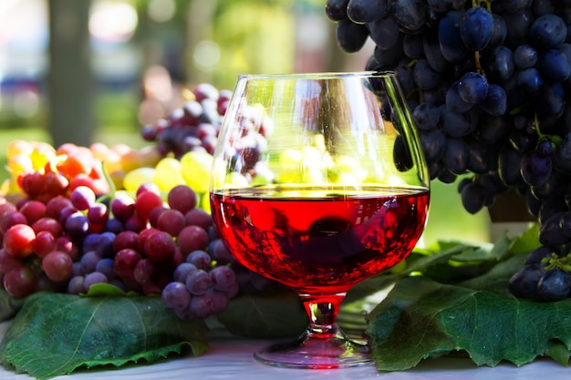 Kieliszek wina i kiść winogron. czerwone wino w szklance