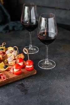 Kieliszek wina i talerz serów z przekąskami wielkości porcji