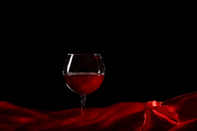 Kieliszek wina na czerwonym jedwabiu z ciemnym tłem
