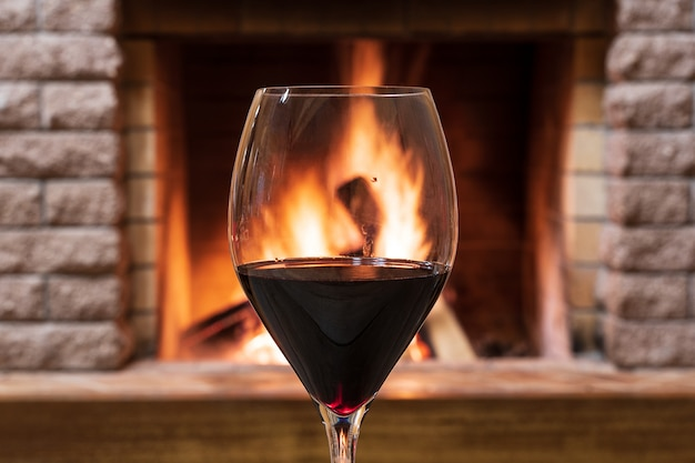 Kieliszek wina na tle przytulnym kominkiem, koncepcja hygge.