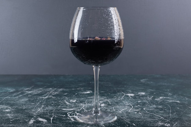 Kieliszek wina z lodem na niebieskim stole.