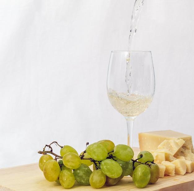 Kieliszek włoskiego białego wina podany z parmezanem i winogronami na drewnianej desce do krojenia z białym tłem