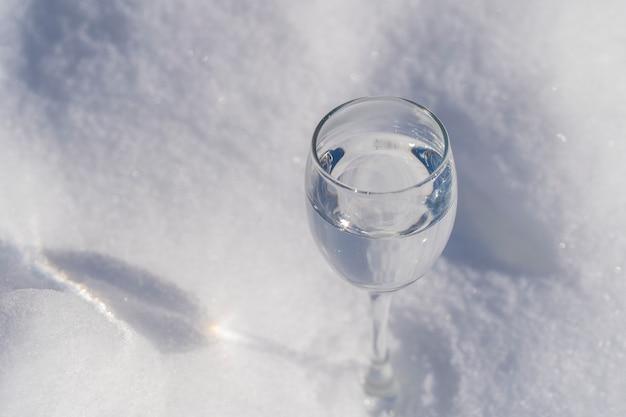 Kieliszek wódki na białym śniegu zimą, zbliżenie, ukraina