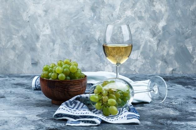 Kieliszek z bliska białych winogron ze szklanką whisky, miska winogron, ręcznik kuchenny na ciemnym i jasnoniebieskim tle marmuru. poziomy
