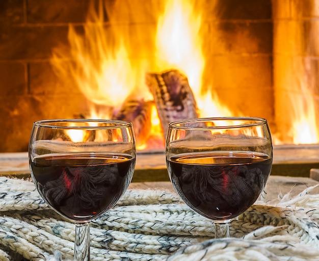 Kieliszki czerwonego wina przed przytulnym kominkiem.