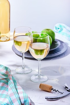Kieliszki do białego wina i talerz zielonych jabłek