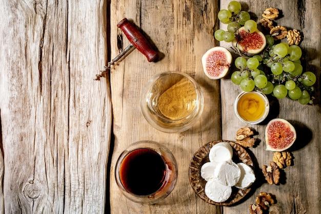 Kieliszki do czerwonego i białego wina z winogronami, figami, kozim serem i orzechami na starym drewnianym tle. leżał płasko, kopia przestrzeń