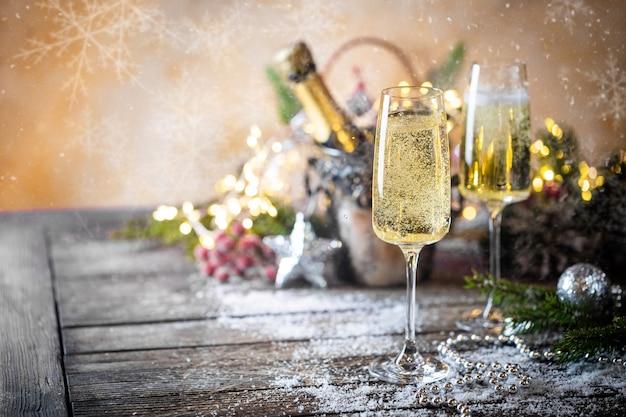 Kieliszki do szampana i świąteczny wystrój na błyszczącym świątecznym tle