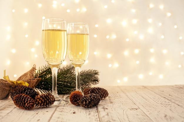 Kieliszki do szampana na drewnianym stole z niewyraźną złotą girlandą, koncepcja sylwestra