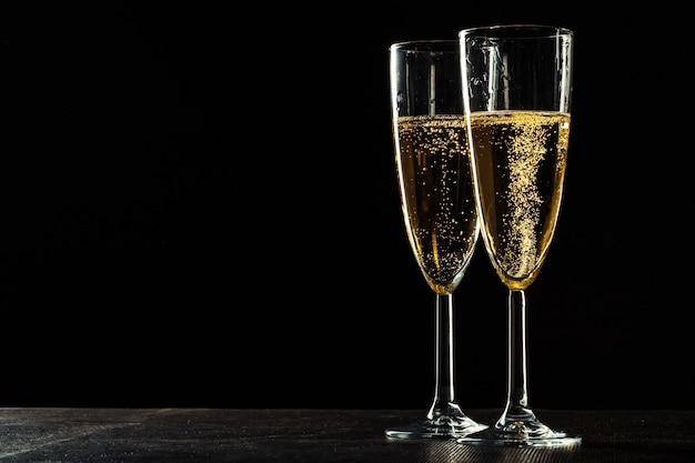 Kieliszki do szampana na świąteczną okazję na ciemnym tle