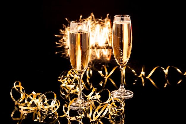 Kieliszki do szampana przed świątecznymi światłami