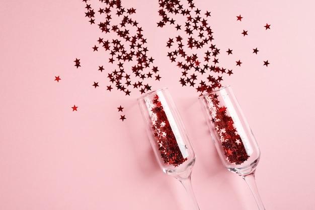 Kieliszki do szampana z czerwonym konfetti na różowym tle.
