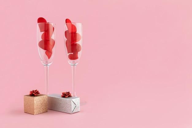 Kieliszki do szampana z czerwonymi sercami i prezent na różowo. 14 lutego. szczęśliwy obiad walentynkowy.