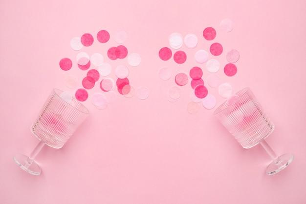 Kieliszki do szampana z różowym konfetti na różowym tle papieru w stylu minimalistycznym. płaska kompozycja świecka na urodziny, dzień matki lub wesele widok z góry