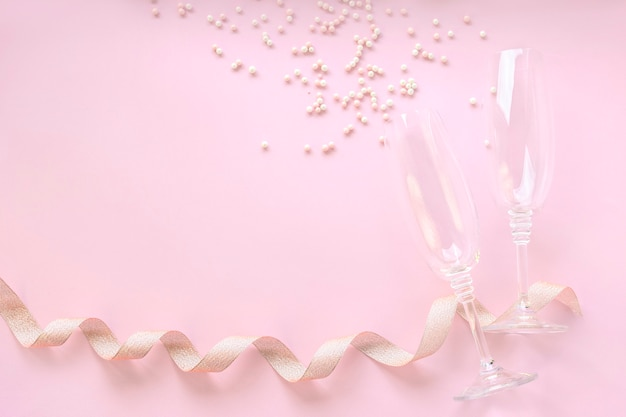 Kieliszki do szampana z rozrzuconymi białymi perłami i złotą taśmą.