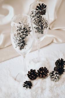 Kieliszki do szampana ze zdobionymi szyszkami na białym śniegu. ozdoby świąteczne. szczęśliwego nowego roku. skopiuj miejsce. świece. domowy wystrój diy. boże narodzenie zero odpadów