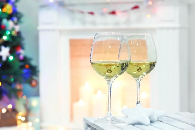 Kieliszki do wina z świątecznym wystrojem na kominku