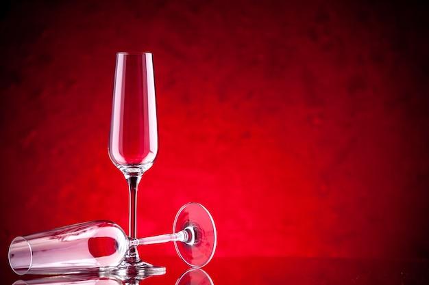Kieliszki do wina z widokiem z przodu, jeden jest przewrócony