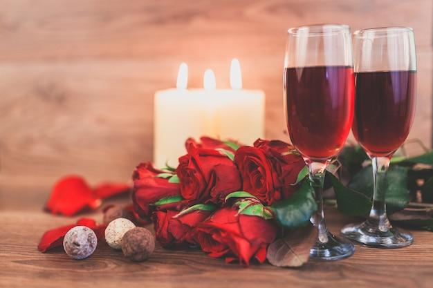 Kieliszki do wina z zapalonymi świecami i bukiet róż