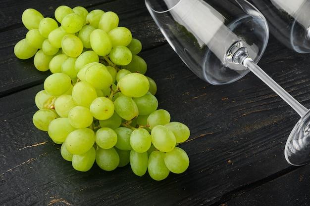 Kieliszki do wina z zestawem winogron, na czarnym drewnianym stole