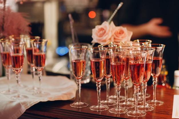 Kieliszki różowego wina musującego na barowym biurku.