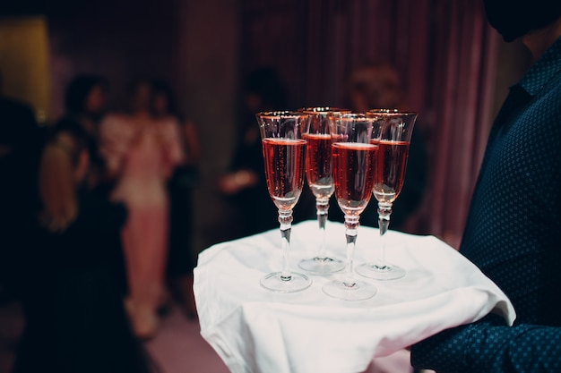 Kieliszki różowego wina musującego na naczynie strony kelnera
