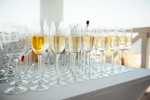 Kieliszki szampana na bankiecie, białe wino musujące w kieliszkach do wina, świąteczny nastrój.