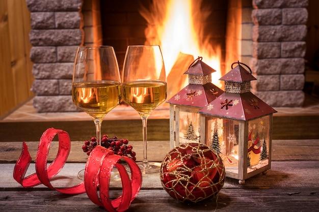 Kieliszki wina i świece przy kominku