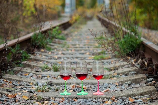 Kieliszki wina na torach kolejowych. stare szyny toru vintage tło z alkoholem odchodzi. pojedynczy tor kolejowy przez las lub las. koncepcja podróży. skopiuj miejsce na stronę