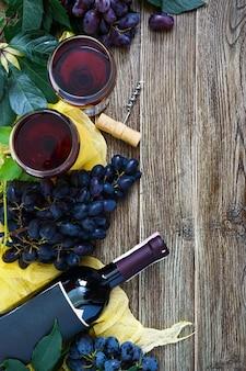 Kieliszki z czerwonym winem, butelka, korkociąg, niebieskie winogrona, liście na drewnianym stole. wino tło z miejsca na kopię. widok z góry, układ płaski