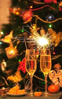 Kieliszki z szampanem i ognie na tle udekorowanej choinki