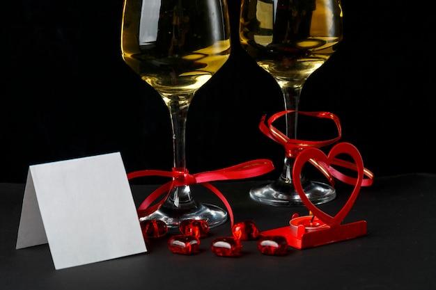 Kieliszki z szampanem przewiązane czerwoną wstążką, kartka okolicznościowa i świecznik w kształcie serca