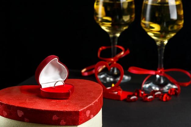 Kieliszki z szampanem przewiązane czerwoną wstążką na czarnym tle pudełka w kształcie serca z prezentami i pierścionkiem. poziome zdjęcie
