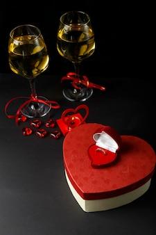 Kieliszki z szampanem przewiązane czerwoną wstążką, pudełka w kształcie serca z prezentem i pierścionkiem.