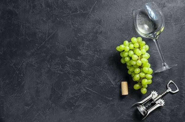 Kieliszki z winogronami i korkami. koncepcja produkcji wina. czarne tło