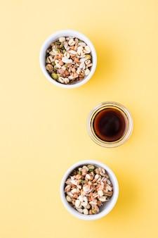 Kiełkujące ziarna fasoli mung, soczewicy, nasion lnu i słonecznika oraz sosu sojowego w miseczkach na żółtym stole.