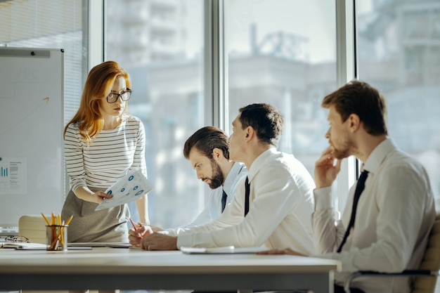 Kiepska wydajność. surowa młoda szefowa jest niezadowolona z wyników pracy swoich pracowników i pokazuje błędy w raportach, gdy czują się zawstydzeni