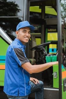 Kierowca autobusu w mundurze i czapce uśmiechnął się do kamery, gdy wszedł do drzwi autobusu