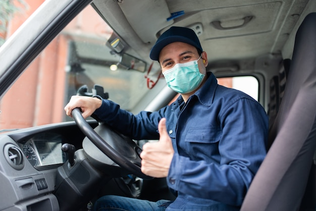 Kierowca ciężarówki daje kciuki do góry podczas pandemii koronawirusa