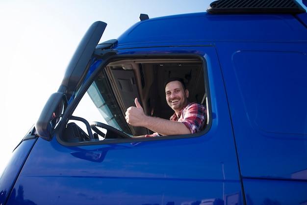 Kierowca ciężarówki pokazuje kciuki przez okno kabiny